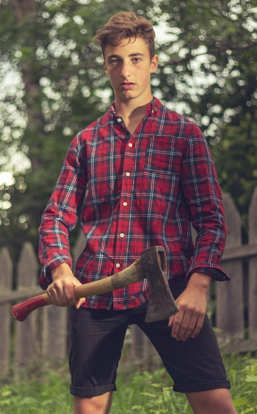 Serious man with axe standing in rural garden