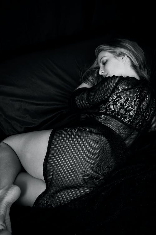 Grayscale Photo of Woman Lying Down In Black Lingerie