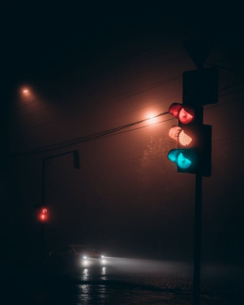 Automobile with glowing headlights on road near illuminated traffic light at foggy night