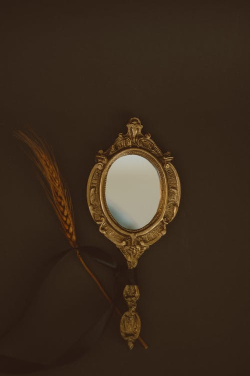 Oval Gold Framed Mirror on Black Surface