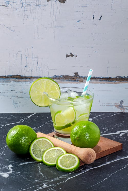 Drinking Glass with Lime Juice and Ice Cubes