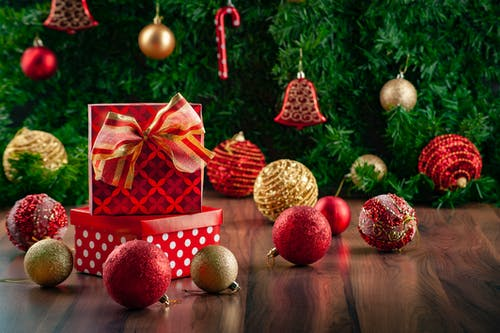 Close-Up Photo of Christmas Balls and Presents on a Wooden Floor