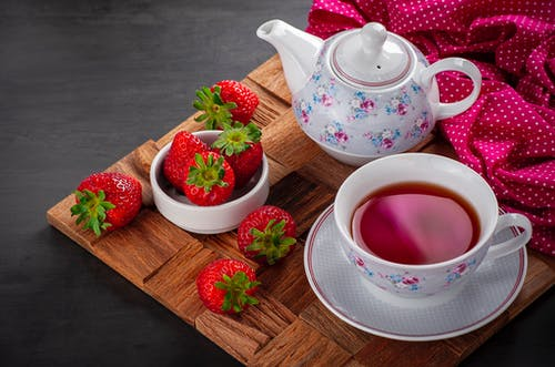 A Cup of Strawberry Tea Near Strawberries