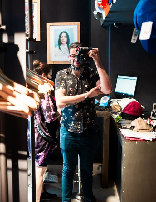 Man Inside a Clothing Store Holding a Camera Over His Eye