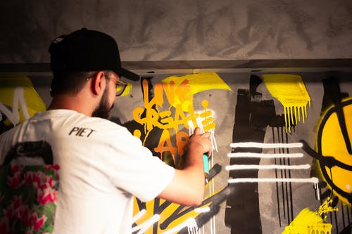 Photo of a Man in a Black Cap Spraying Paint on a Wall