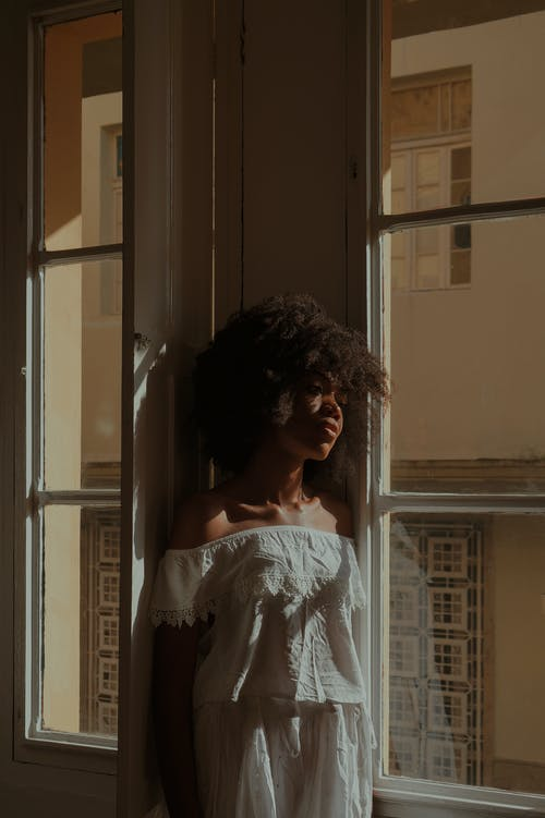 Thoughtful black lady standing near window
