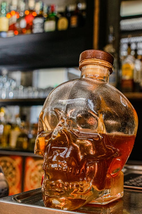 Clear Skull Shaped Glass Bottle With Brown Liquid Inside