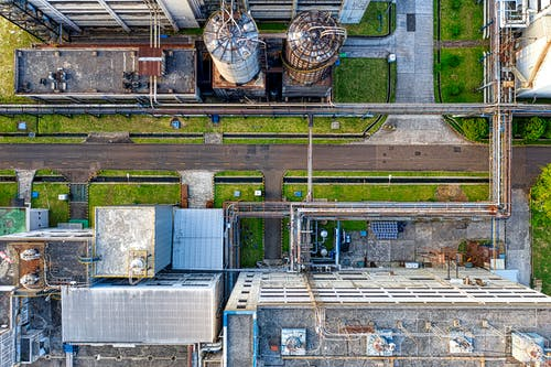 Aerial view of old factory with tanks and facility for industrial production located along road