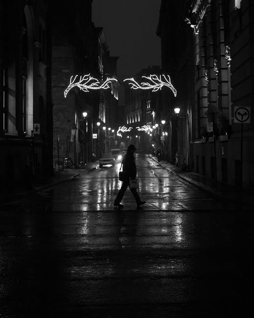 Silhouette of Person Walking on Street during Night Time