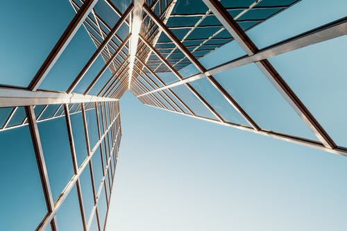From below of multistory geometric building with glass mirrored windows reflecting cloudless blue sky on sunny day