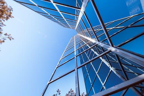 Exterior of futuristic skyscraper with glass mirrored walls under blue sky