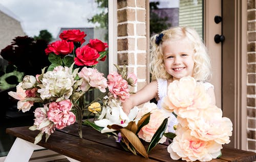 Smiling child in white clothes looking at camera while spending time on terrace at table near house with bouquet of flowers in daytime