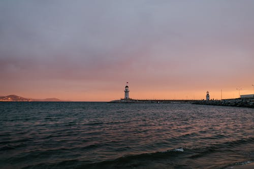 Picturesque scenery of rippling tranquil sea washing seacoast with white lighthouse under cloudy blue and pink sky at sundown