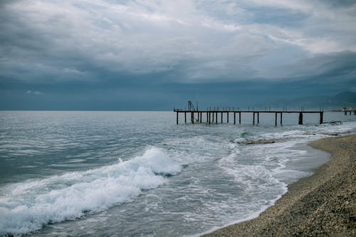 Scenery of endless blue sea waving on sandy beach with wooden pier beneath dramatic cloudy sky on overcast stormy weather