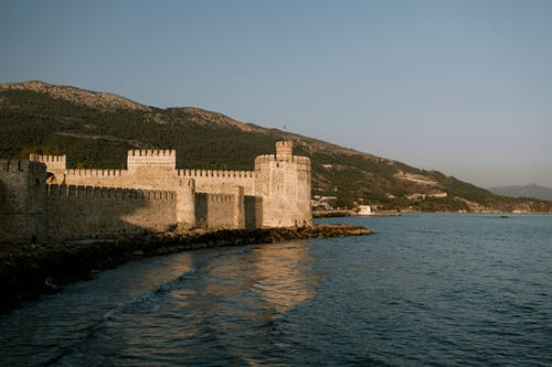 Medieval fortress on seashore against grassy hill