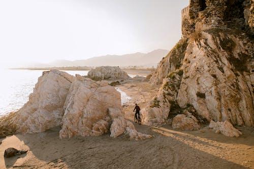 Pessoa Caminhando Na Areia Cinzenta Perto Da Formação Rochosa Marrom