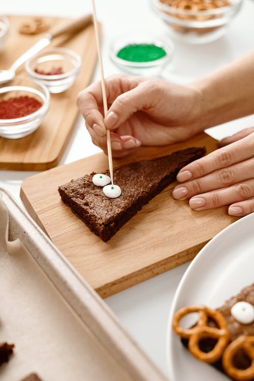 Person Decorating a Triangle Shaped Brown Cake