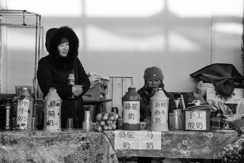 Woman in Black Jacket Sitting on the Floor With Bottles in Grayscale Photography