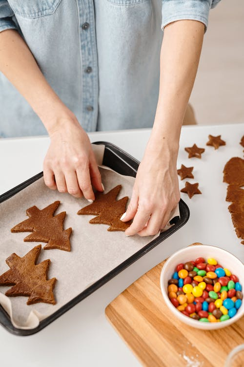 Person Putting Christmas Tree Shaped Cookies on a Tray
