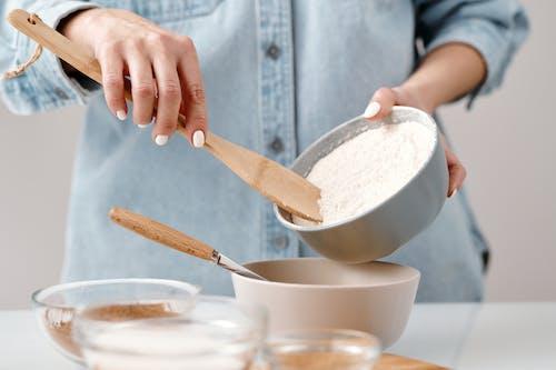 Person Adding Flour into a Bowl