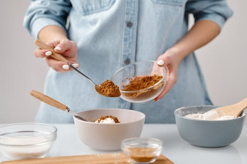 Person Adding a Spoon of Cinnamon in a Bowl