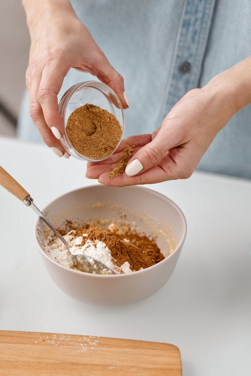 Person Adding Cinnamon in a Bowl