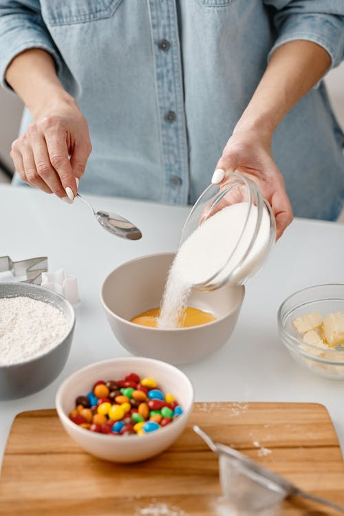 Person Pouring Powdered Sugar in a Bowl