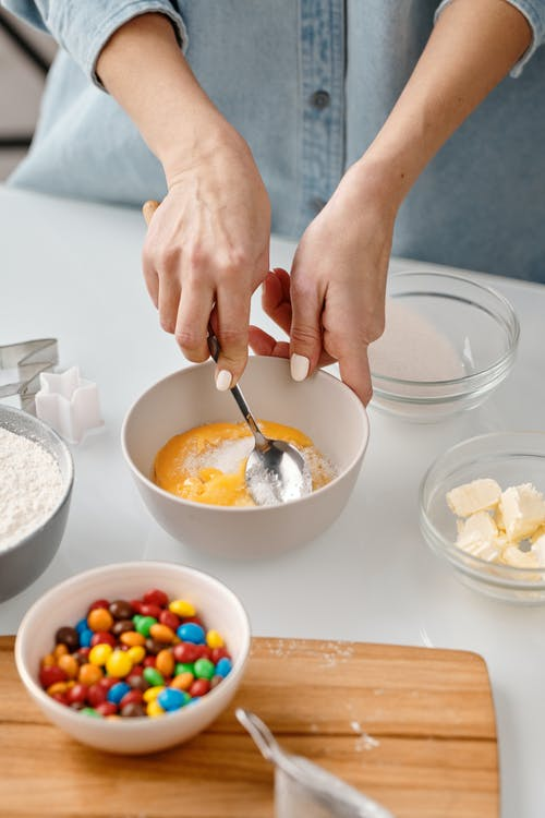 Person Mixing Yellow Eggs in a Bowl