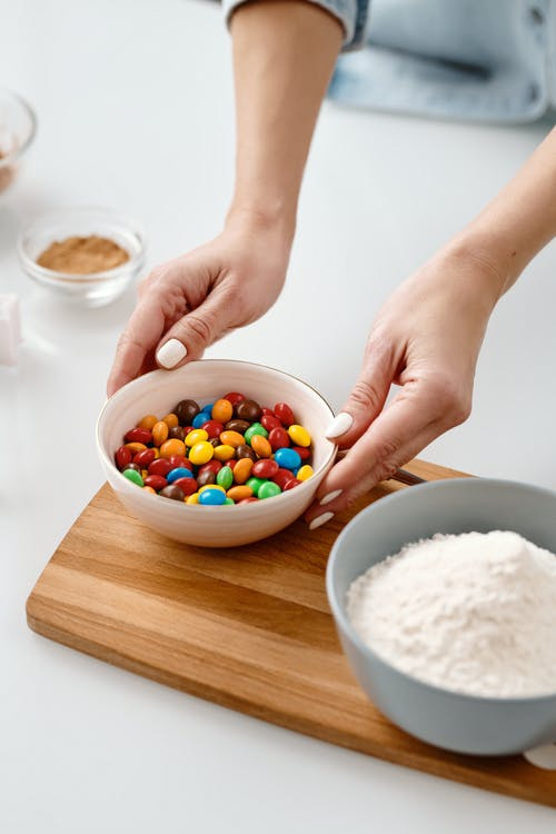 Person Holding a Ceramic Bowl With Chocolate Candies