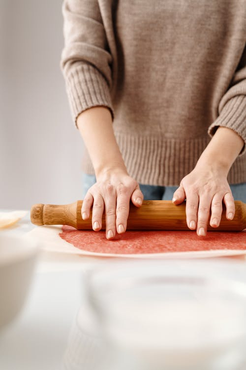 Person Flattening a Dough With Rolling Pin
