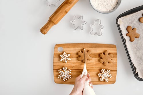 Person Decorating a Snowflakes Shaped Cookies