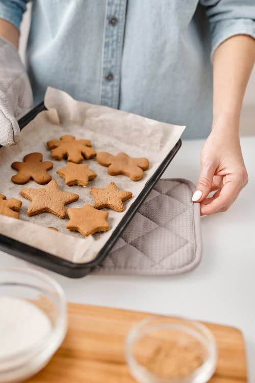 Person Holding a Tray With Different Shapes of Brown Cookies
