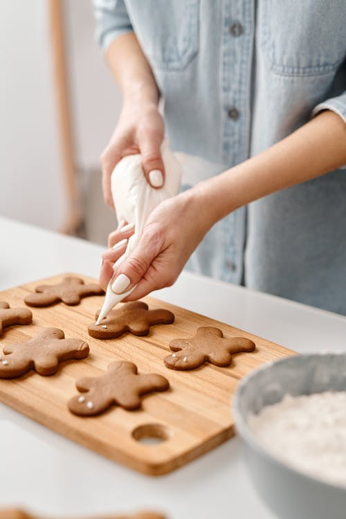 Person Decorating a Gingerbread Man Cookies