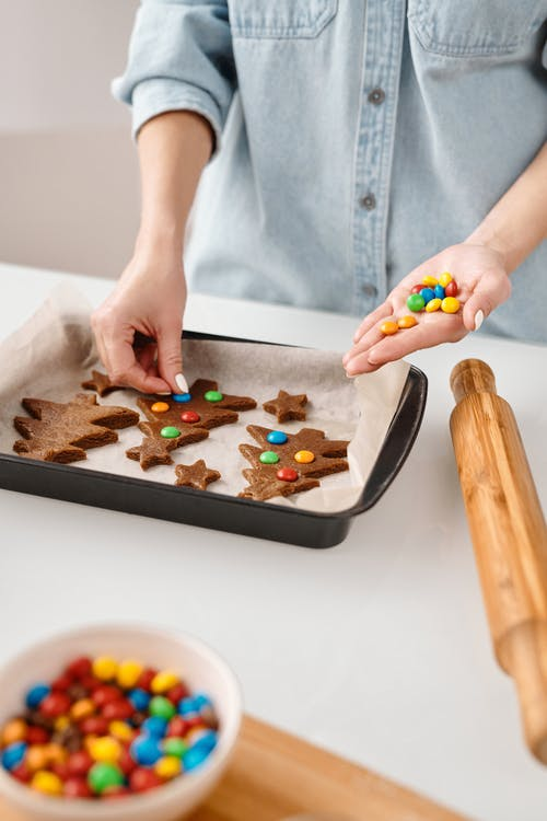 Person Decorating a Christmas Tree Shaped Cookies