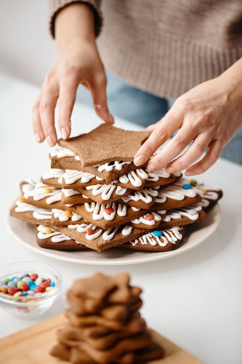 Person Putting Brown Star Shaped Cookie on Top