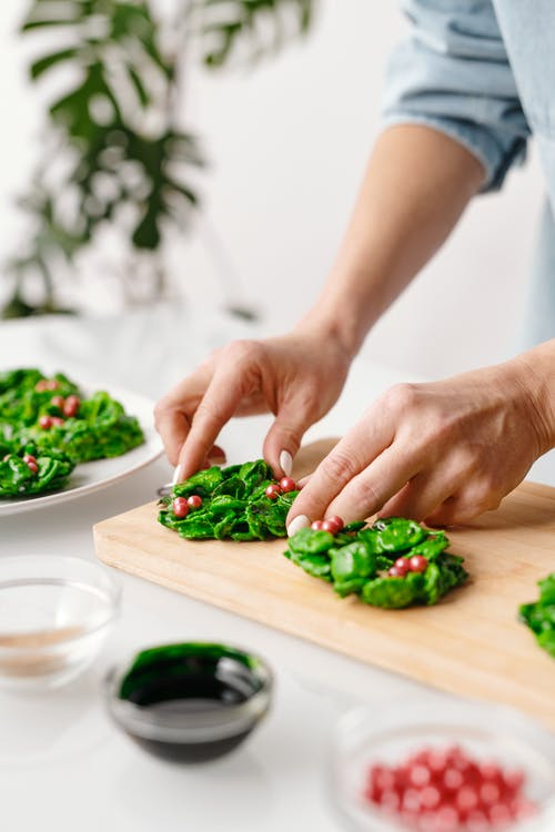 Person Putting Fresh Vegetable Salad on a Wooden Tray
