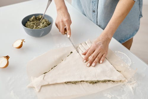 Person Slicing a Christmas Tree Shaped Bread With Fillings