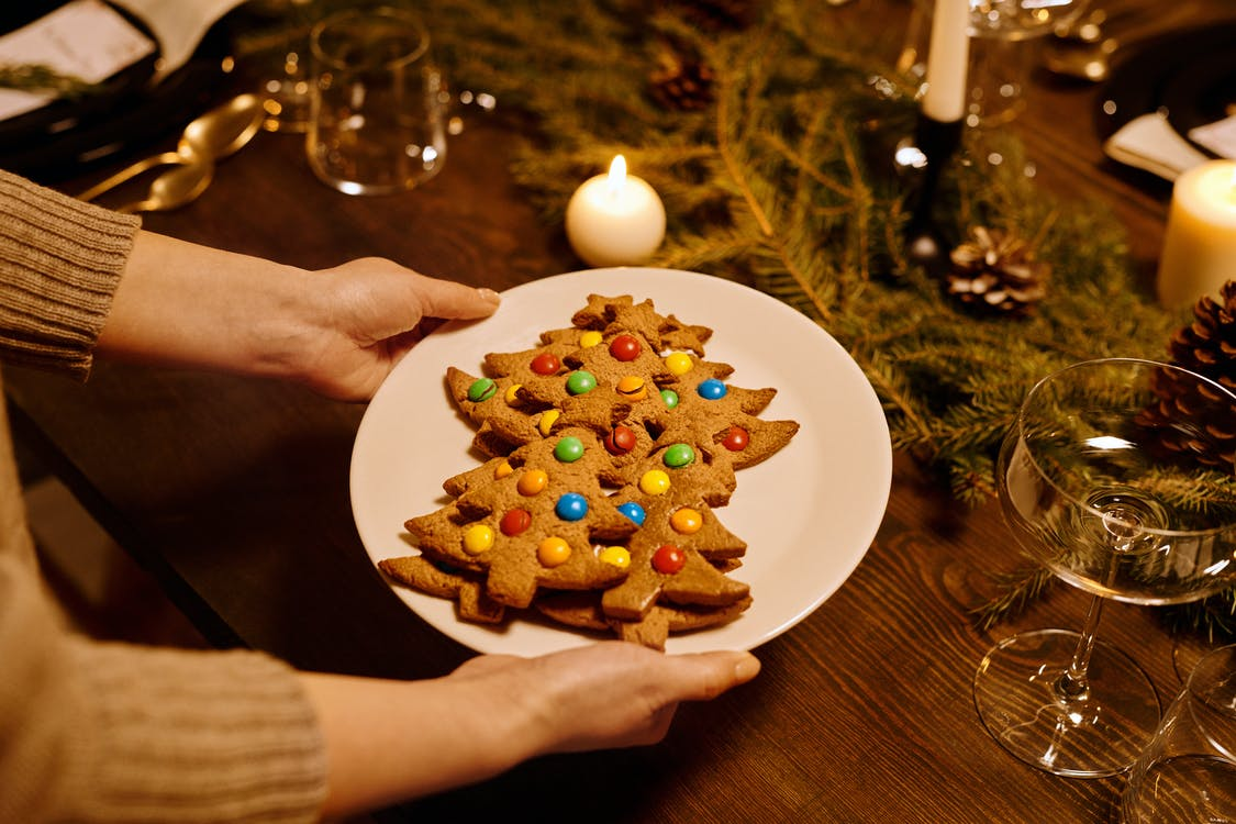 Person Serving a Platter of Christmas Tree Shaped Cookies
