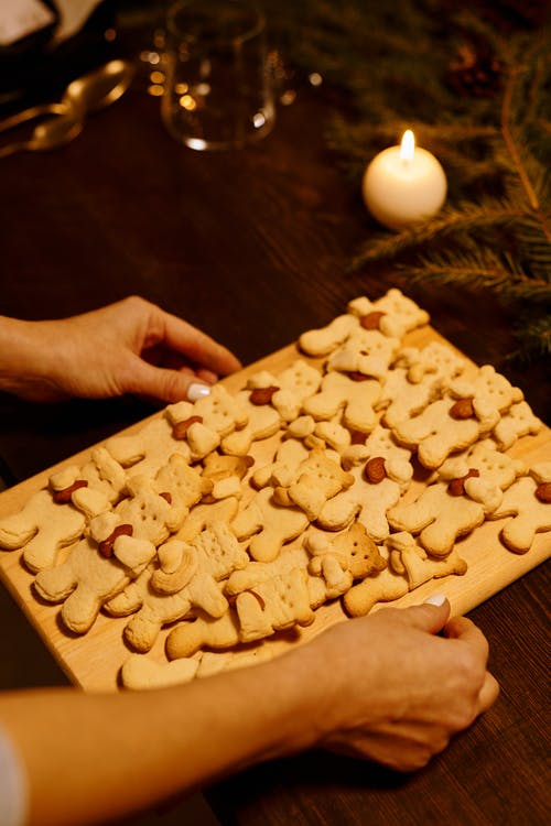 Person Holding a Wooden Tray With Teddy Bear Cookies