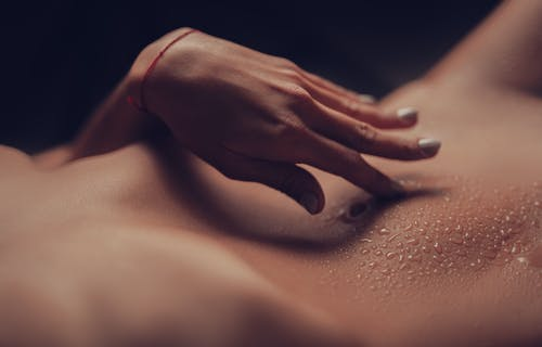 Crop unrecognizable naked female with perfect body touching belly covered with water drops in dark room