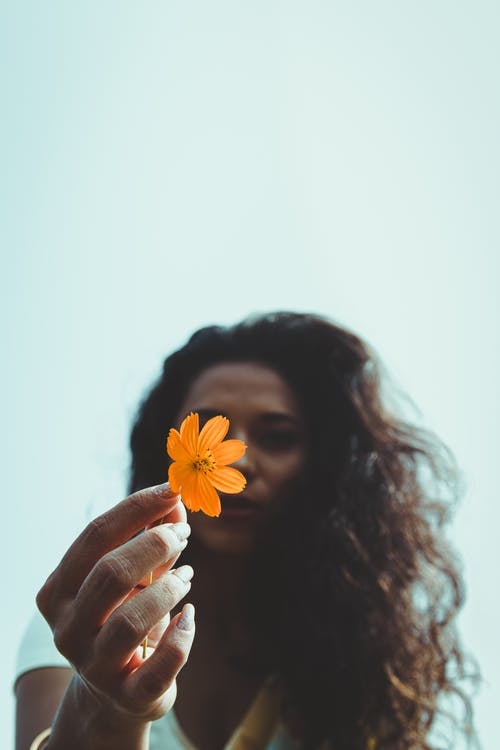Woman holding flower in hand in nature