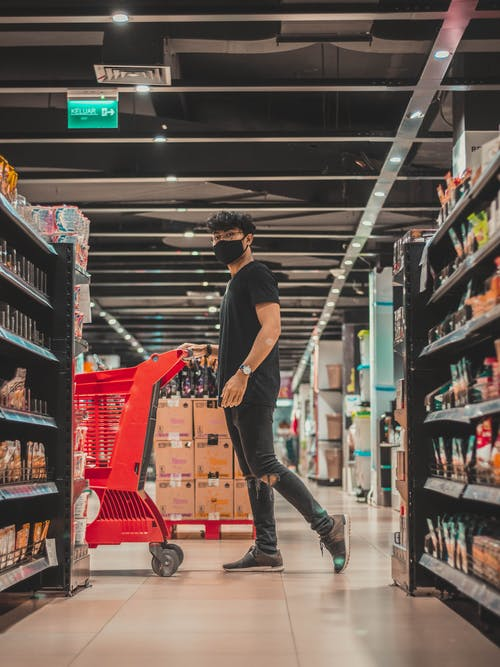Man in mask pushing trolley in supermarket