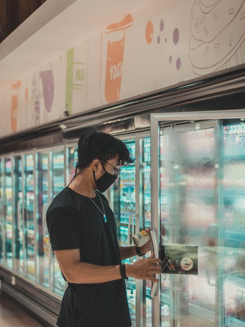 Side view concentrated young male in black shirt and face mask opening fridge door and choosing goods while doing grocery purchases in supermarket