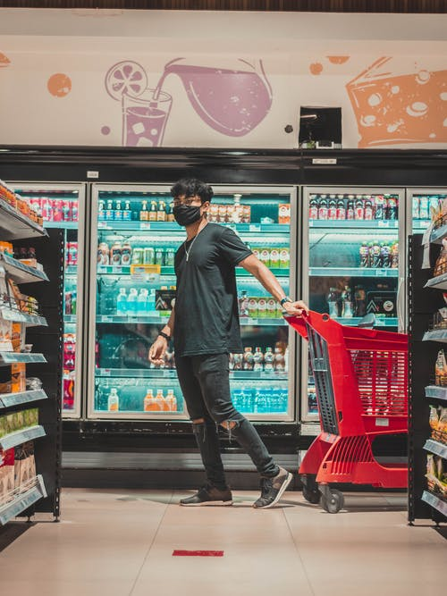 Side view full body emotionless male wearing black casual clothes walking with cart near fridge and shelves with goods in contemporary grocery store