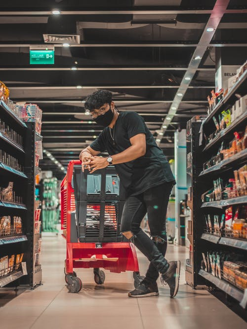 Full length young male wearing black ripped jeans and face mask leaning on cart and looking at camera while standing with legs crossed and looking at camera in grocery shop
