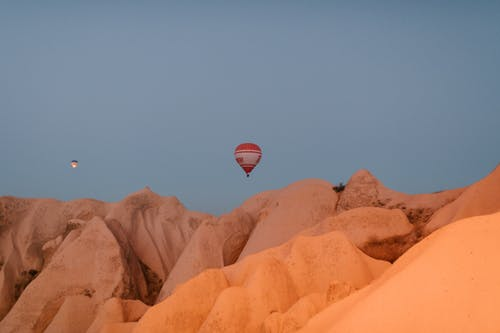 Picturesque view of hot air balloons flying over rocky chimneys with smooth surface in Cappadocia on early morning
