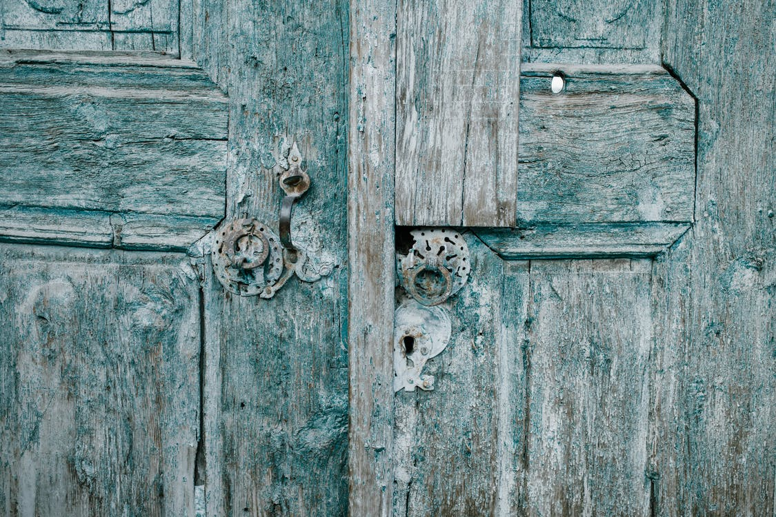 Shabby wooden blue doors with rusted locks