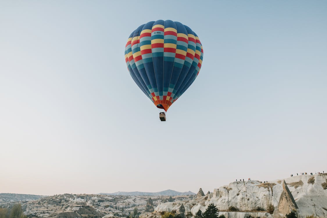 Picturesque scenery of colorful hot air balloon soaring above spacious rocky terrain against cloudless blue sky in early morning