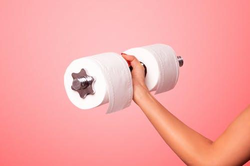 Белый рулон туалетной бумаги на розовой поверхности
