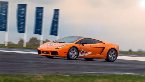 Modern luxury orange sports car riding fast on asphalt highway at race at daytime under bright sky